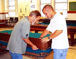 Cagle's Billiards employee repairing pool table felt