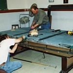 Cagle's Billiards employees installing billiard table lighting